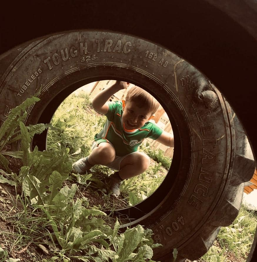Child peeking through a tyre at Muck Angels